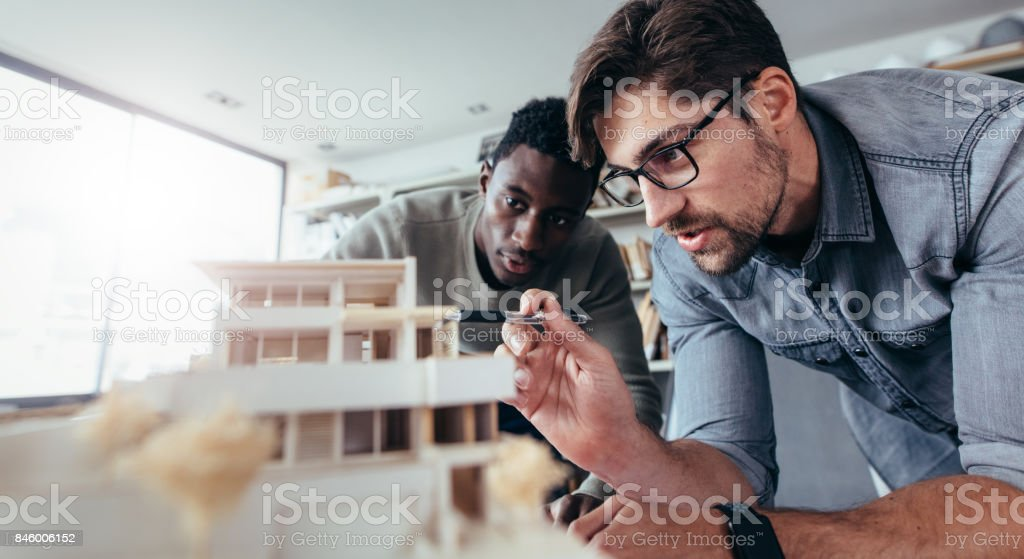 Two male architects discussing over house model stock photo