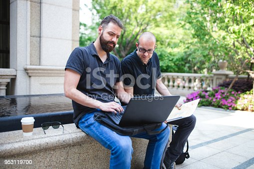 Two Male Architects Going Over Plan And Using Laptop Outside Of Business Building