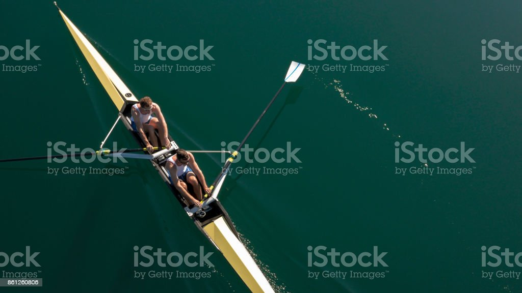 Two male athletes sculling on lake in sunshine stock photo