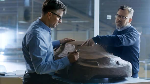 zwei männliche automobil-designer arbeitet an einem tonmodell der neuen generation elektroauto zukunft entwerfen. hält einen tablet-pc für grafik-design, andere mit lehm mit rake/draht formt. - skulpturprojekte stock-fotos und bilder