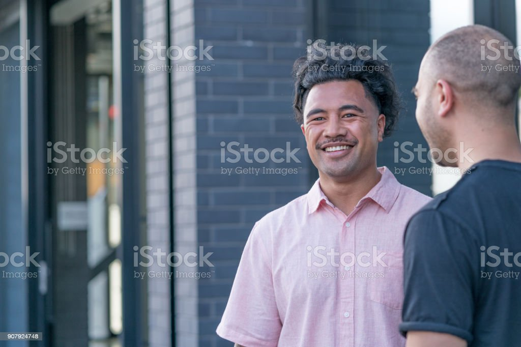 Two male business colleagues share a joke outside the office royalty-free stock photo