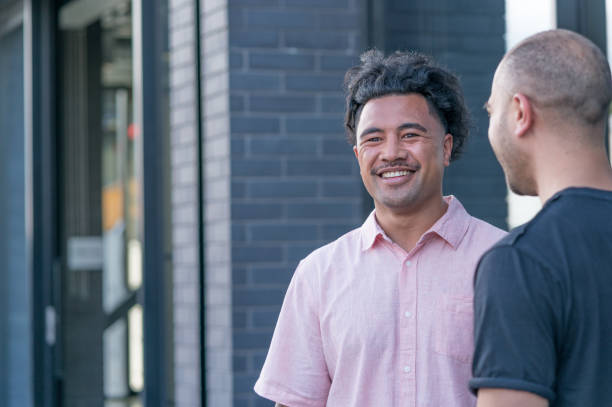 two male business colleagues share a joke outside the office - pacific islander ethnicity stock photos and pictures