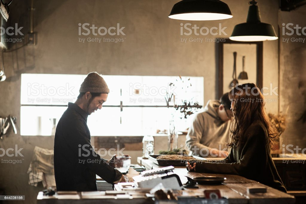Two male cafe owners preparing coffee in coffee shop stock photo