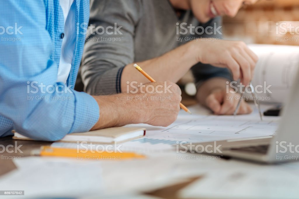 Two male colleagues creating a blueprint together stock photo