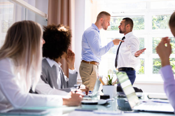 Two Male Colleagues Fighting In Office stock photo
