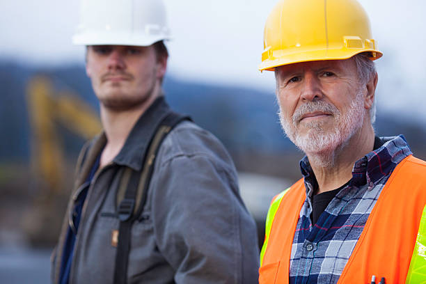 Two male construction workers on a job site. stock photo
