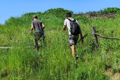 istock Two male fishermen climb a hill in the tall spring and summer grass 1255672573