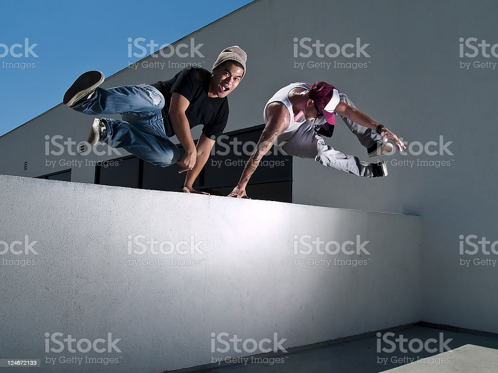Two Male Freerunners Jumping Over a Wall Performing Parkour stock photo