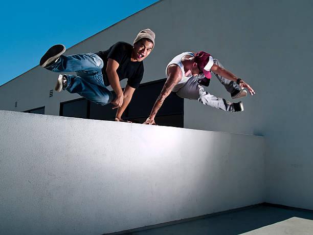 zwei männliche freerunner springt über die mauer performing parkour - parkour stock-fotos und bilder