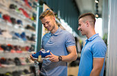 istock Two male friends buy sports shoes together 836473286