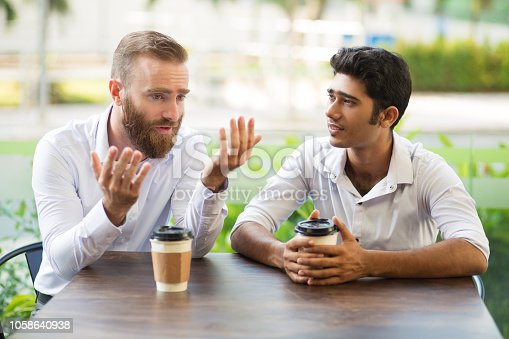 istock Two male friends drinking coffee and talking in outdoor cafe 1058640938