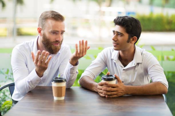dwóch mężczyzn przyjaciół picia kawy i rozmowy w kawiarni na świeżym powietrzu - dwie osoby zdjęcia i obrazy z banku zdjęć