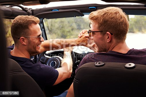 istock Two Male Friends Driving Open Top Car On Country Road 639707080