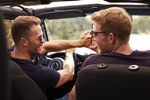 Two Male Friends Driving Open Top Car On Country Road stock photo