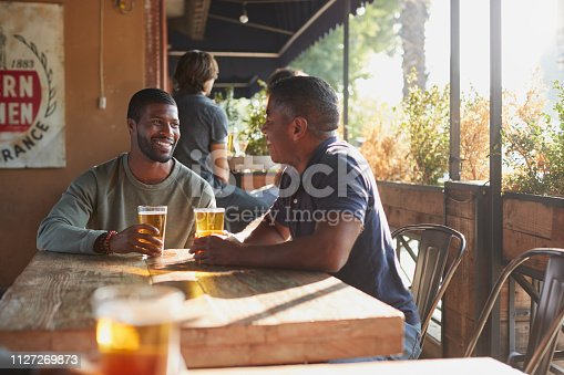 istock Two Male Friends Meeting In Sports Bar Enjoying Drink Before Game 1127269873