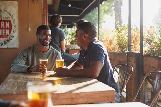 Two Male Friends Meeting In Sports Bar Enjoying Drink Before Game stock photo