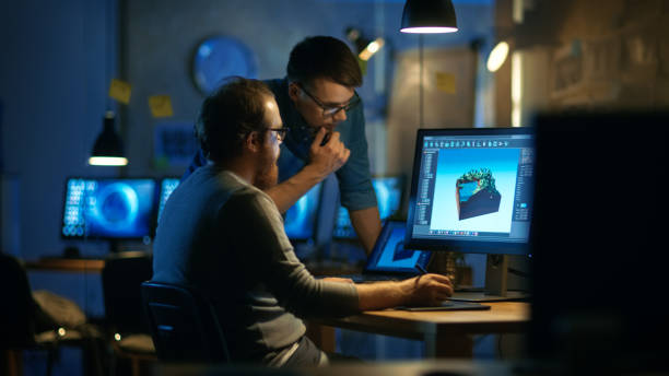 two male game developers discuss game level drawing, one uses graphic tablet. they work late at night in a loft office. - ingegnere foto e immagini stock