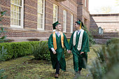Two male graduates holding hands