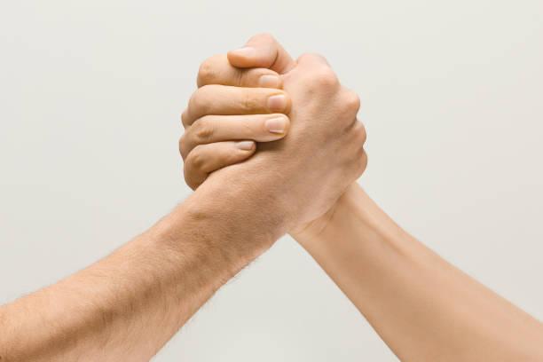 Zwei männliche Hände, die sich im Armwrestling auf grauem Studio-Hintergrund vereinzelt – Foto