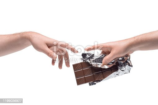 istock Two male hands passing one another chocolate bar in foil on white background 1199036927