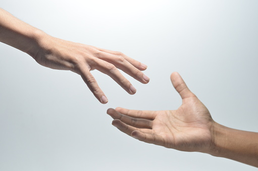 Two male hands reaching towards each other on isolated white background
