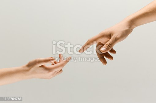 974882202istockphoto Two male hands trying to touch isolated on grey studio background 1142764785