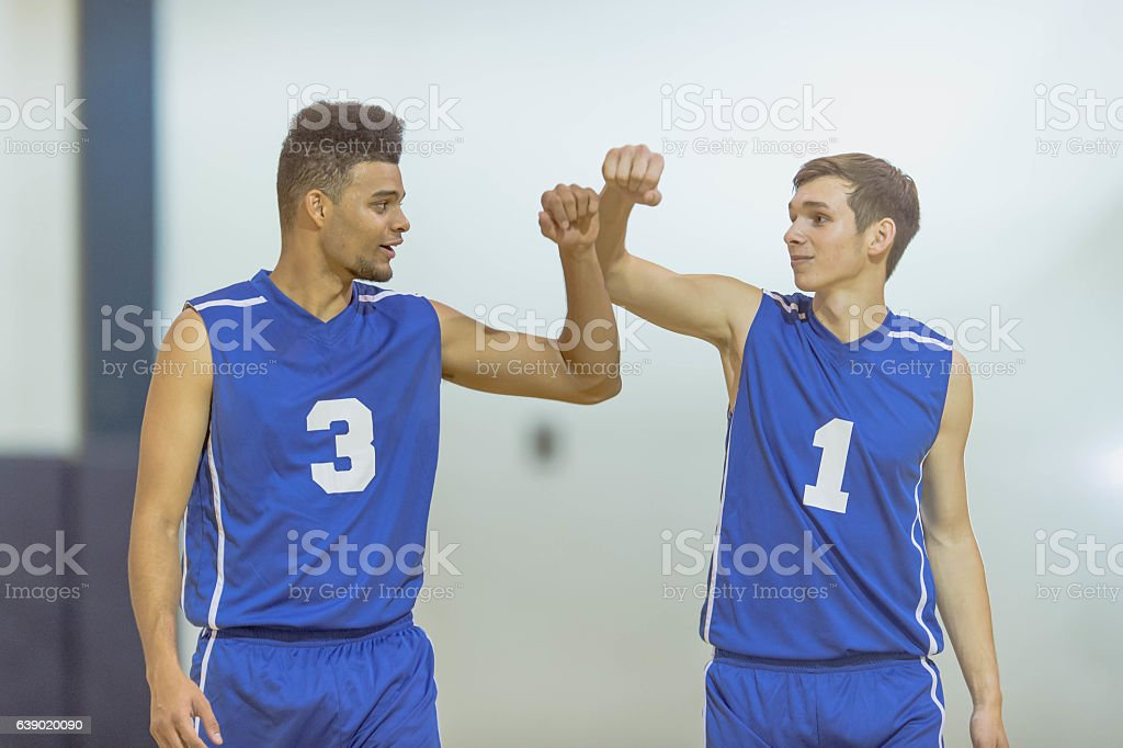 Two male high school basketball players high fiving during a game