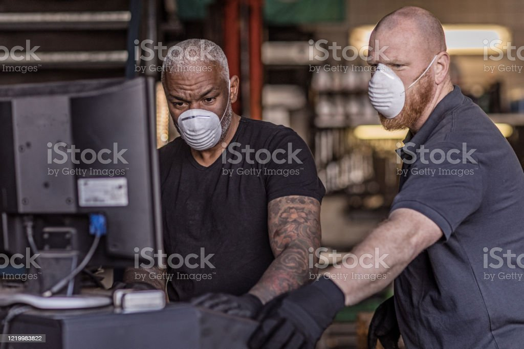 Two male mechanic essential workers wearing a face mask each during virus outbreak Two mixed race male mechanic essential workers wearing a face mask each and gloves, whilst continuing to work in their auto repair shop, during virus outbreak 2020 Stock Photo