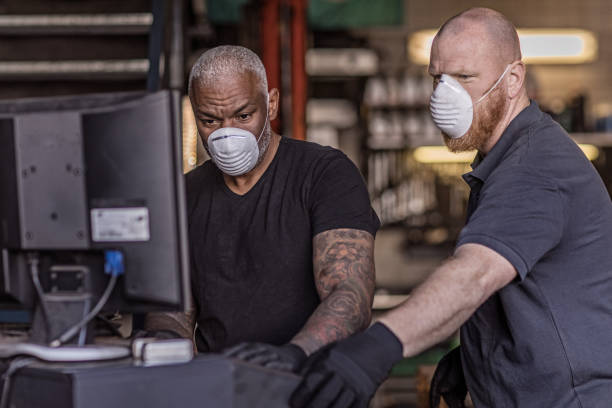 two male mechanic essential workers wearing a face mask each during virus outbreak - servizi essenziali foto e immagini stock