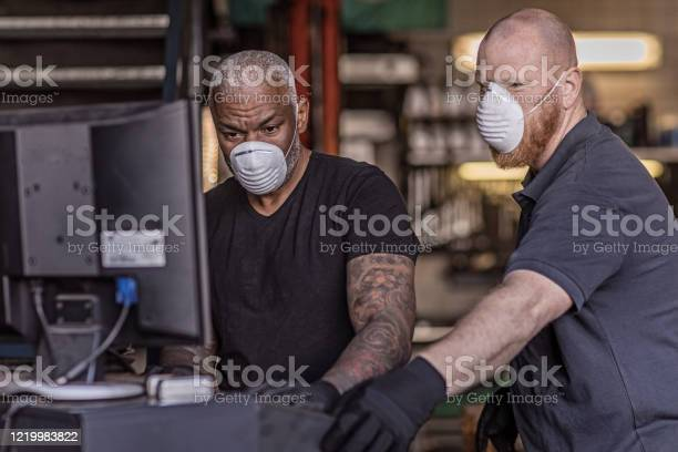 Two Male Mechanic Essential Workers Wearing A Face Mask Each During Virus Outbreak Stock Photo - Download Image Now