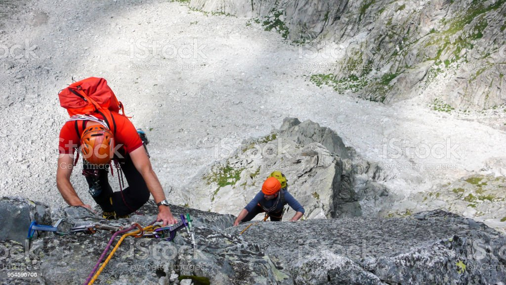 two male rock climbers on a granite climbing route in the high alpine peaks of southeastern Switzerland stock photo