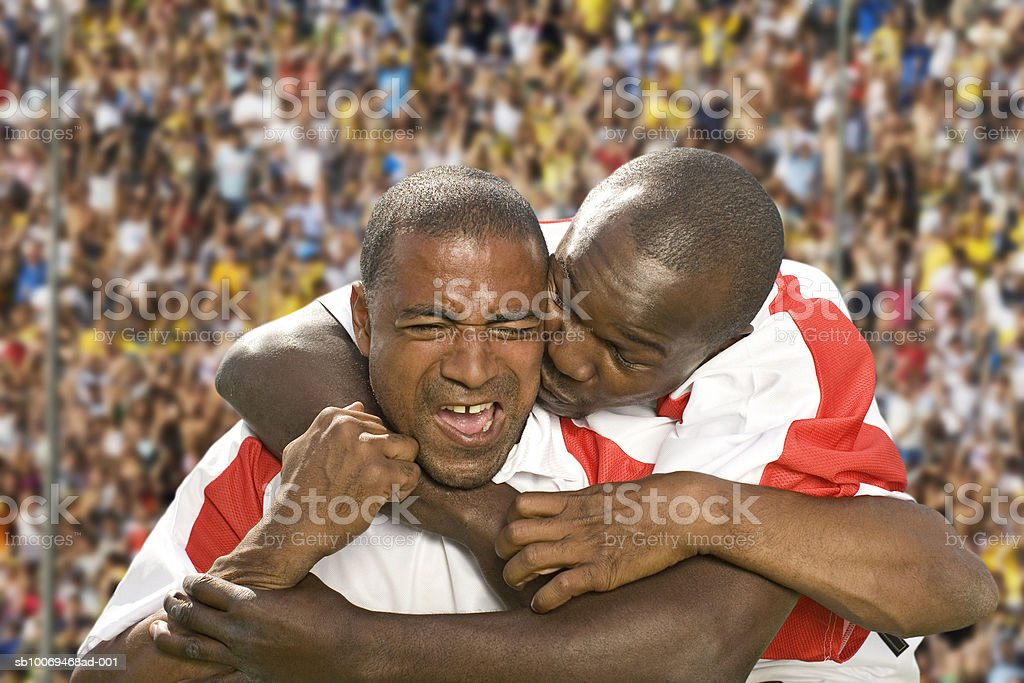 Two male soccer players embracing in stadium royalty-free stock photo
