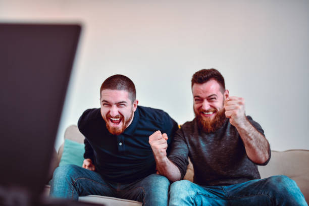 Two Male Sports Fans Enjoying Tense Soccer Match Two Male Sports Fans Enjoying Tense Soccer Match man cave couch stock pictures, royalty-free photos & images