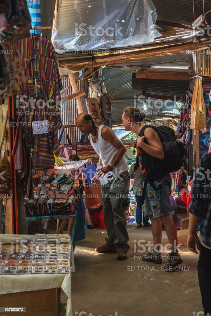 Two male tourists choosing souvenirs at Doi Pui hill tribe village, handicraft market of the ethnic minority of miao or hmong or maew people in Chianf Mai province, Northern Thailand stock photo