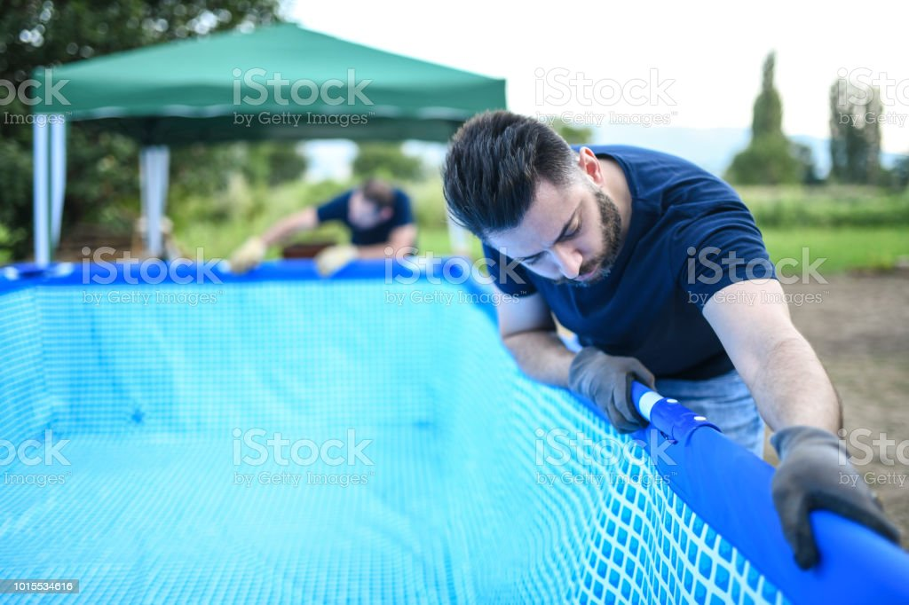 Two Male Workers Setting Up Swimming Pool In Backyard Stock Photo
