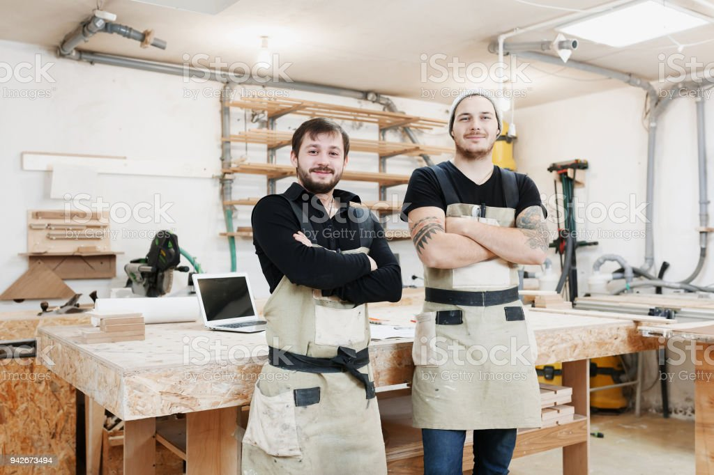 Two male workers working in furniture industry and creating custom...