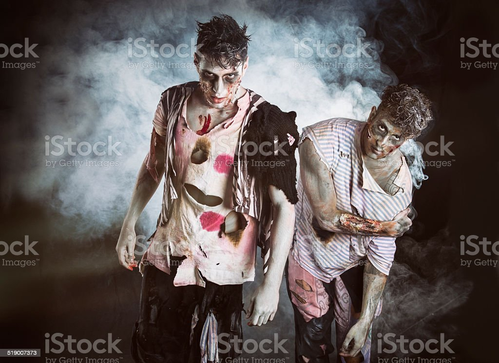 Two male zombies standing on black smoky background stock photo