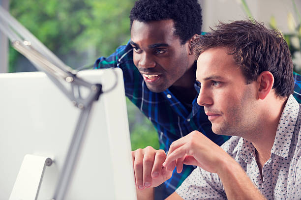 two males work together on computer stock photo