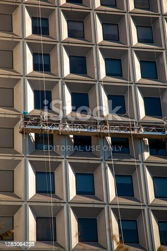New York, NY, USA 11/26/2017: Two man are seen on an elevated platform hanging on the side of a skyscraper. These workers wearing belts and helmets are cleaning the windows at a high elevation.