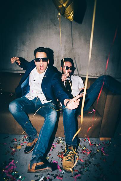 two man at a party - club sofa stock-fotos und bilder