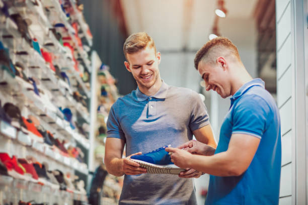 Two man deciding on new sports shoes in sports store Two man deciding on new sports shoes in sports store studded stock pictures, royalty-free photos & images