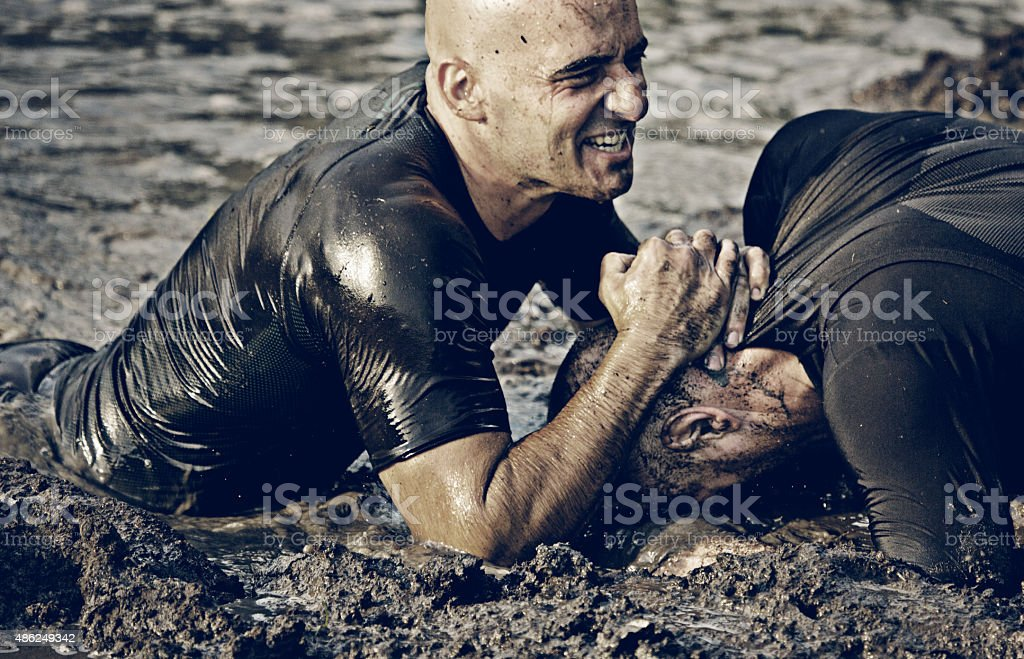 two man fighting in mud stock photo