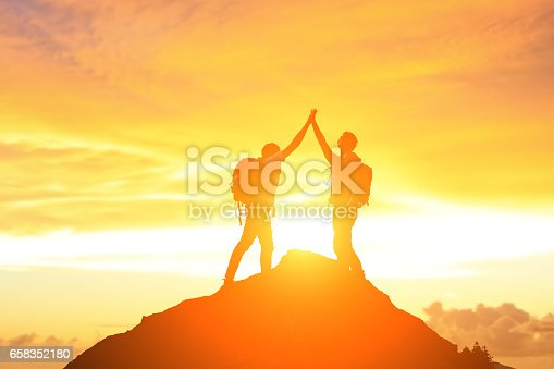two man give five on the moutain with sunrise
