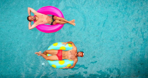 Two man relaxing on inflatable rings Aerial view of a two men relaxing on a inflatable rings and floating in the pool afloat stock pictures, royalty-free photos & images