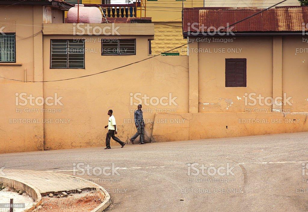 Two man walking by the street of Kumasi, Ghana stock photo