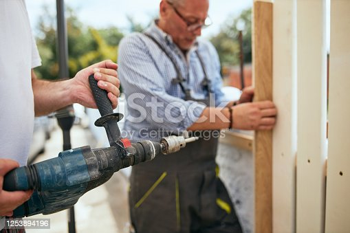 istock Two manual workers installing a wooden fence 1253894196