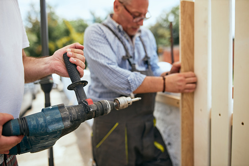 Two skilled construction manual workers installing a wooden fence.