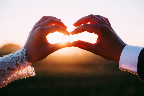 Two married people holding wedding rings at sunset. Two married people holding wedding rings at sunset. wedding stock pictures, royalty-free photos & images
