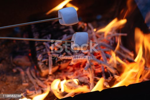 two marshmallows on the skewers roasting over the flames at the evening