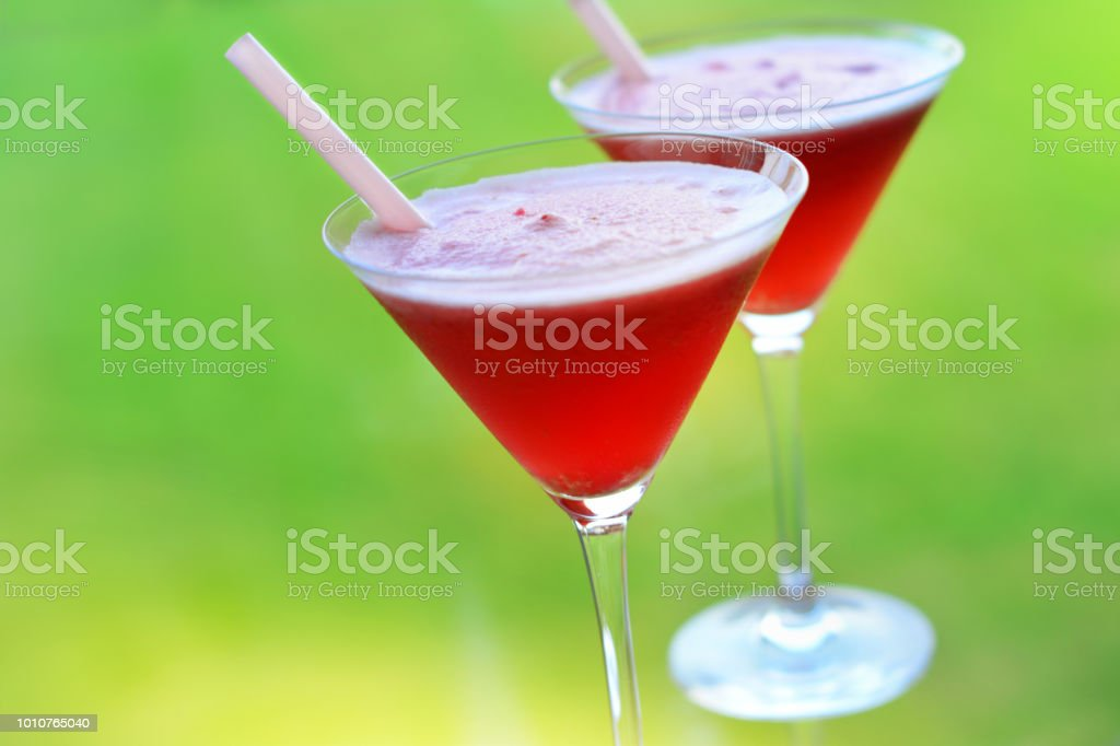 Two martini shape glasses with straws filled with red chilled drink on green background
